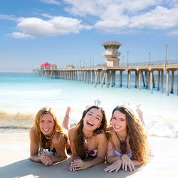 a pier and three smiling women sitting in the sand