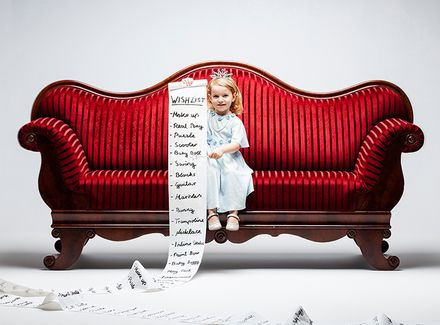 a little girl on a big red couch holding a long list
