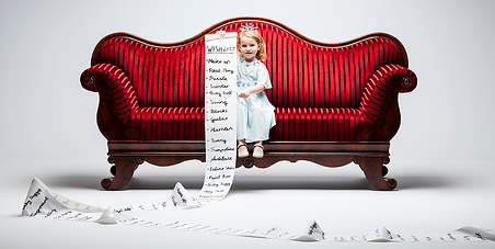 A little girl on a red couch holding a long list